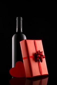 Подарочная коробка и бутылка вина, изолированные на черном