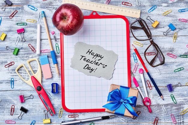 Подарочная коробка, яблоко и карта. канцелярские товары и буфер обмена. поздравления с днем учителя от студентов.