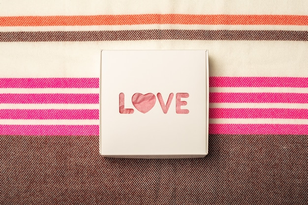Gift box on the background of a multicolored fabric texture. composition valentine's day. banner. flat lay, top view.