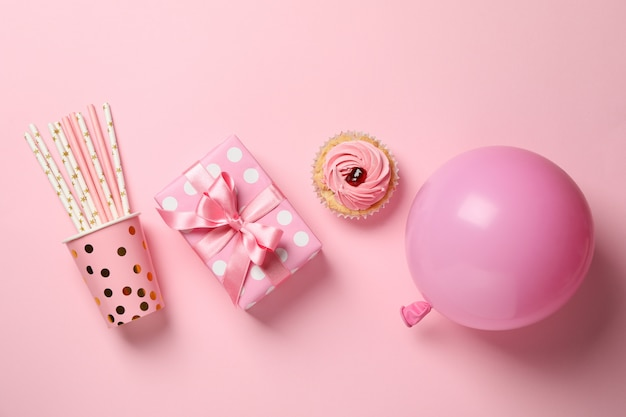 Gift box, balloon, cupcake and paper cup with straws on pink background, top view