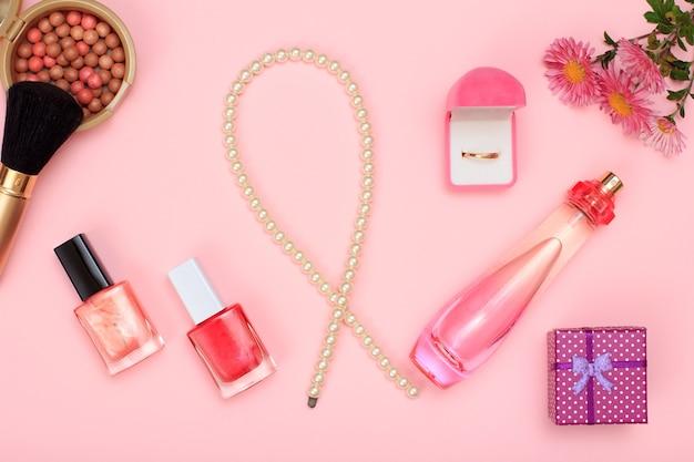 ギフトボックス、ビーズ、香水のボトル、マニキュア、ボックス内の金の指輪、ピンクの背景にブラシ付きのパウダー。女性の化粧品とアクセサリー。上面図。
