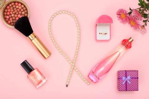ギフトボックス、ビーズ、香水のボトル、マニキュア、ボックス内の金の指輪、ピンクの背景にブラシ付きのパウダー。女性の香水、化粧品、アクセサリー。上面図。