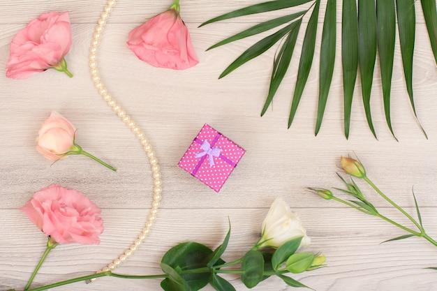 선물 상자, 흰색과 분홍색 꽃이 있는 끈에 있는 구슬, 나무 배경에 녹색 잎. 여성화장품. 평면도.