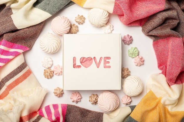 Gift box, beautiful scarf, meringues and sweets on a light background. composition valentine's day. banner. flat lay, top view.