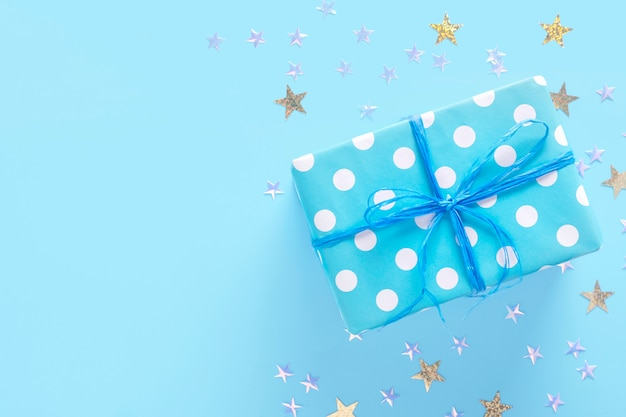 Gift box on a blue surface with stars