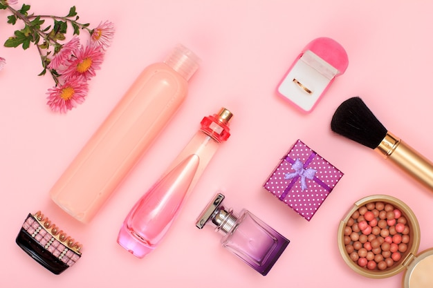 ギフトボックス、香水とシャンプーのボトル、ヘアグリップ、ボックス内の金色のリング、ピンクの背景にブラシ付きのパウダー。女性の化粧品とアクセサリー。上面図。