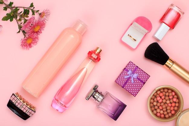 ギフトボックス、香水とシャンプーのボトル、ヘアグリップ、ボックス内の金色のリング、マニキュア、ピンクの背景にブラシ付きのパウダー。女性の化粧品とアクセサリー。上面図。