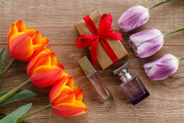 선물 상자, 나무 판자에 빨간색과 라일락 튤립이 있는 향수 병. 인사말 카드 개념입니다. 평면도.