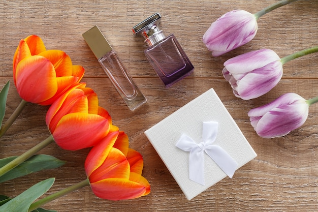 Gift box, bottles of perfume with red and lilac tulips on the wooden boards