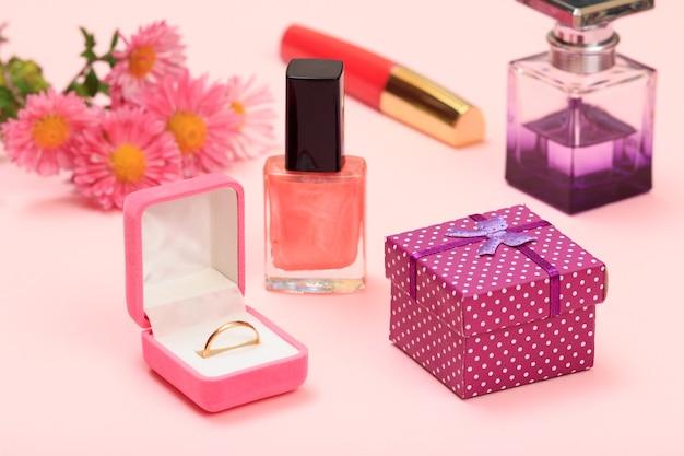 ギフトボックス、マニキュアと香水のボトル、口紅、ボックス内の金の指輪、ピンクの背景の花。女性の化粧品とアクセサリー。
