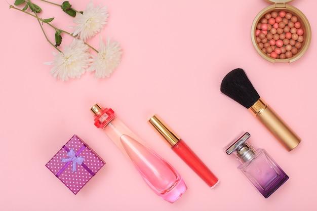 ギフトボックス、香水、ブラシ、口紅、ピンクの背景に粉末のボトル。女性の化粧品とアクセサリー。上面図。
