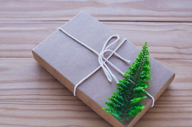 Gift box in brown paper with fern leaves.