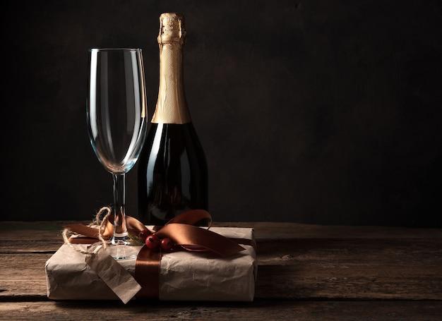 木製のテーブルにギフトボックス、シャンパン、ワイングラス