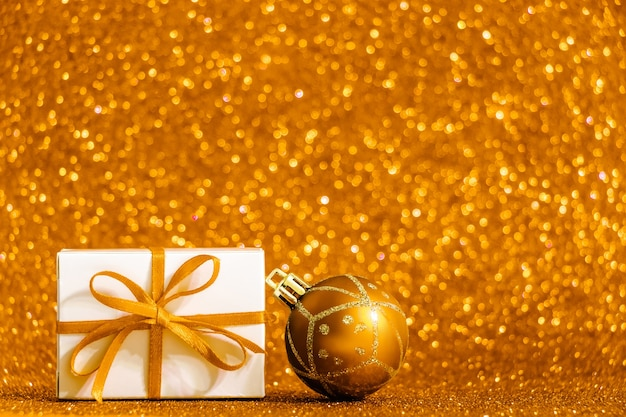 Gift box and christmas ball on shiny gold background. festive concept, place for text.