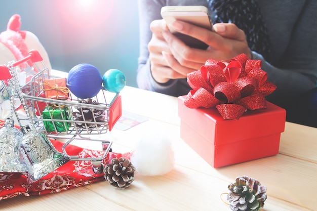 Gift box and christmas ornament on table with woman using mobile phone
