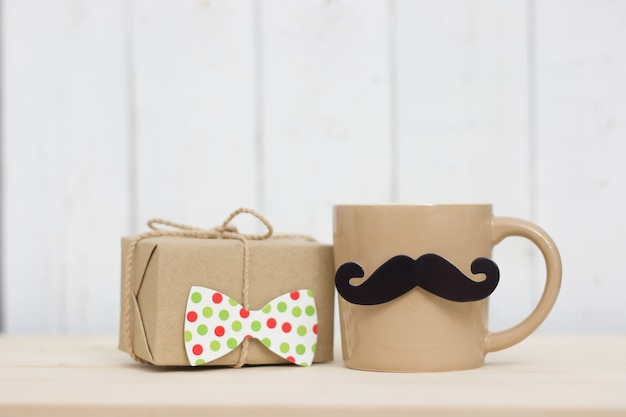 Gift box, coffee cup, paper mustache, tie on wooden background with copy space. happy father's day.