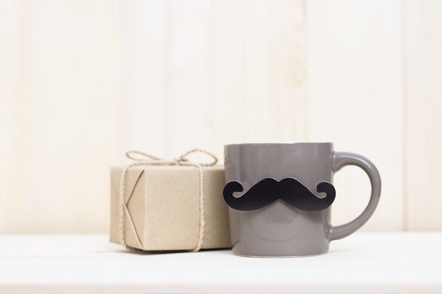 Gift box, coffee cup, paper mustache on wooden background with copy space. happy father's day.