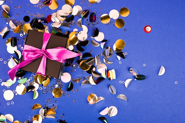 Gift box on a colorful glitter and confetti