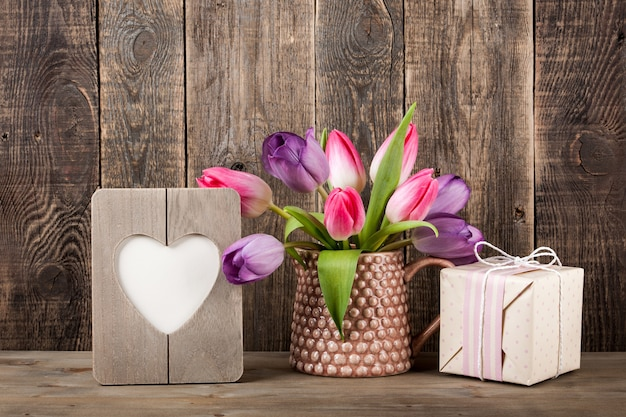 Gift box, colorful tulips and heart shaped frame