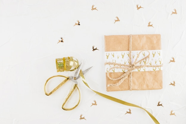 Gift box in craft paper near scissors and ribbon