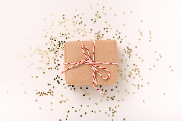 Gift box in craft paper with white-red new year's ribbon and gold candy stars on a beige background