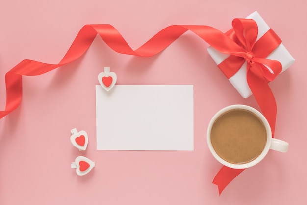 Gift box, cup of coffee, white blank sheet of paper and wooden clips hearts on a pink background. valentine's day concept.
