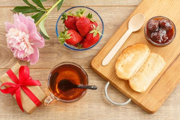 ギフトボックス、お茶、牡丹の花、新鮮なベリー、ガラスのボウルに自家製のイチゴジャム、まな板にトーストとスプーン。上面図。