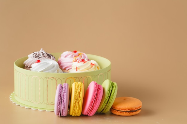 Gift box of cupcakes and colourful macaron on beige