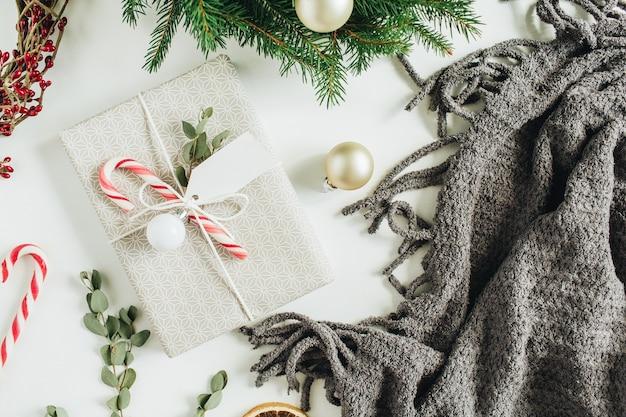 キャンディー、ユーカリ、タグで飾られたギフトボックス。モミの枝と赤いベリーで作られた花輪フレーム。クリスマス休暇の構成。フラットレイ、上面図