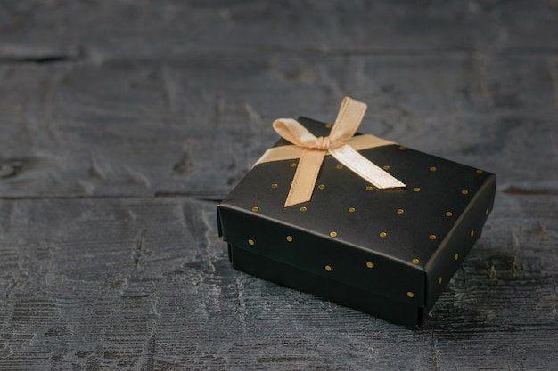 Gift box decorated with gold ribbon on wooden table