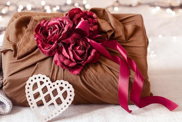 Подарочная коробка украшена лентами и декоративными розочками на вязанных изделиях. оригинальная подарочная упаковка на день всех влюбленных.