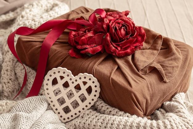 Подарочная коробка, украшенная лентами и декоративными розочками на вязанных изделиях