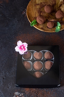 Gift box of delicious chocolate truffles with raw cocoa powder and mint