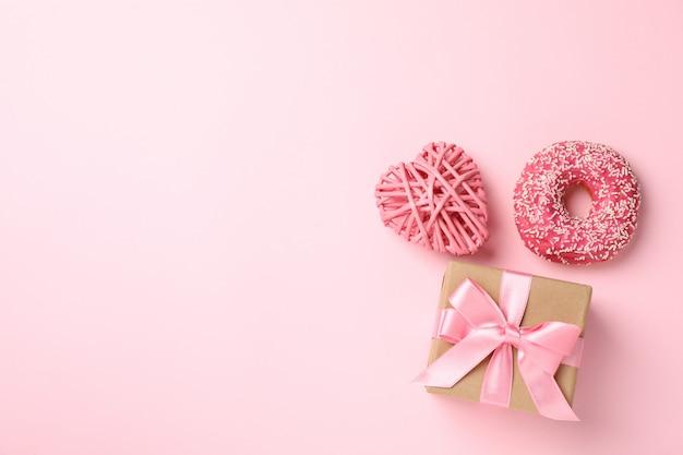 Подарочная коробка, пончик и сердце на розовом фоне, место для текста