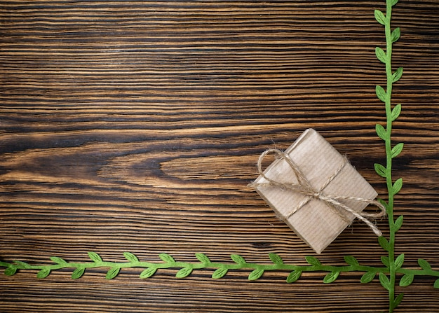 Gift box in eco friendly craft packaging on a natural board decorated with green ribbon with leaves