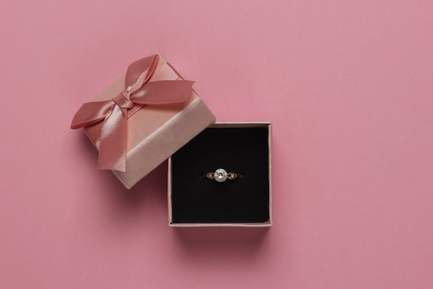 Gift box and engagement gold ring with diamond on pink pastel background. wedding, romantic concept. jewelry. top view. flat lay