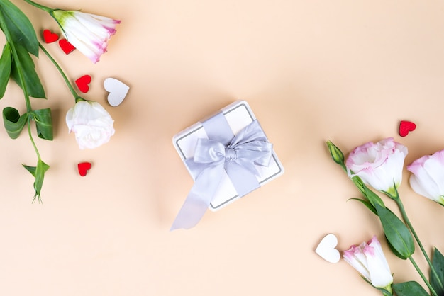 Gift box and eustoma flowers for mothers day or other holidays on beige paper background