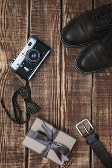Gift box for father's day with men's accessories bow tie, retro camera, belt and leather shoes on a wooden table. flat lay.