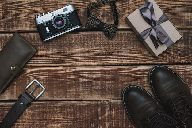 Gift box for father's day with men's accessories bow tie, wallet, retro camera, belt and leather shoes on a wooden table. flat lay.