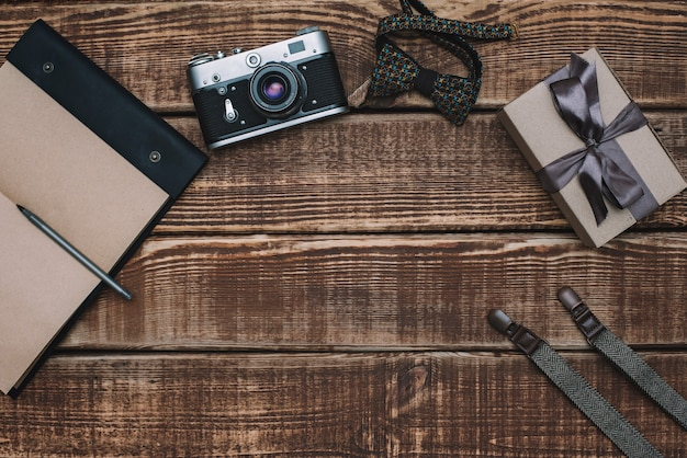 Gift box for father's day with men's accessories bow tie, wallet, retro camera, suspenders and notepad and leather shoes on a wooden table. flat lay.