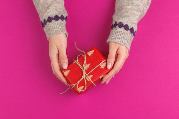 Gift box in female hands on pink background