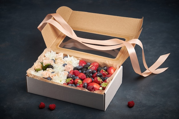 Подарочная коробка с белыми и розовыми цветами и спелыми фруктами на темном фоне