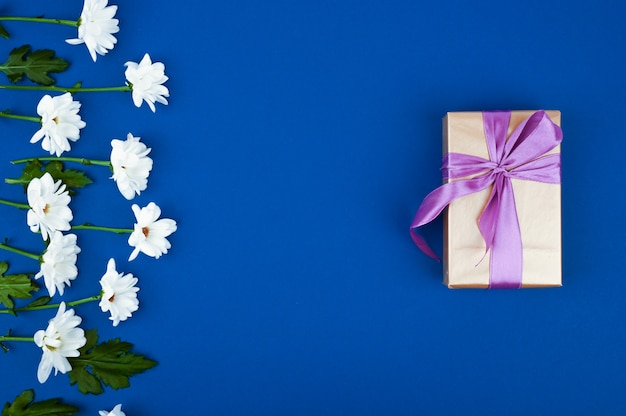 Gift box and flowers on blue table. greeting card for birthday, womans or mothers day. top view