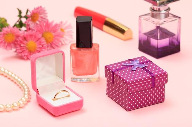 ギフトボックス、花、マニキュアと香水のボトル、口紅、ボックス内の金の指輪、ピンクの背景にビーズ。女性の化粧品とアクセサリー。