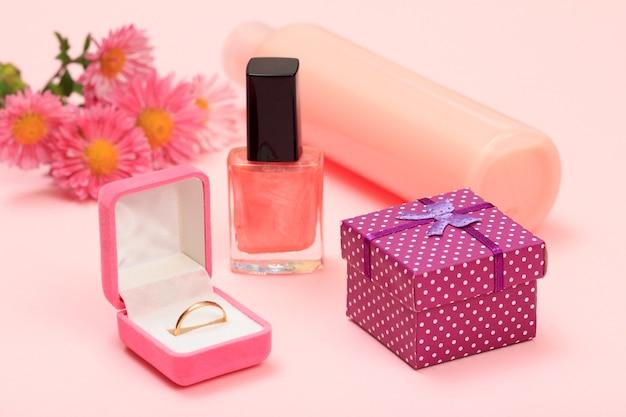 ギフトボックス、花、マニキュアとシャンプーのボトル、ピンクの背景のボックスに金の指輪。女性の化粧品とアクセサリー。