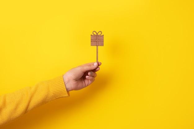 Подарочная коробка на день святого валентина или 8 марта в руке на желтом фоне