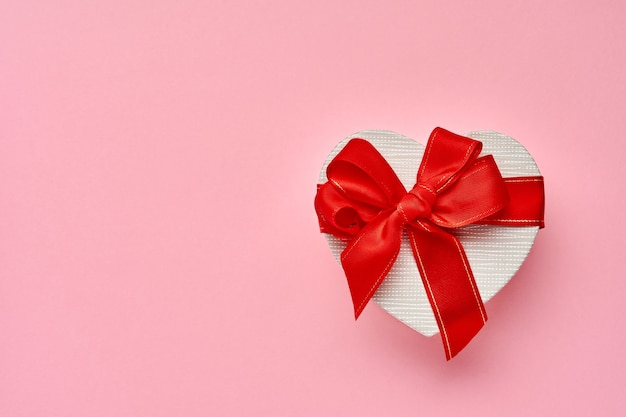 Gift box in the form of heart with a red ribbon on pink background. valentines day concept postcard. top view.