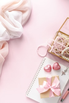 Gift box or gift box and flowers on pink table top view.