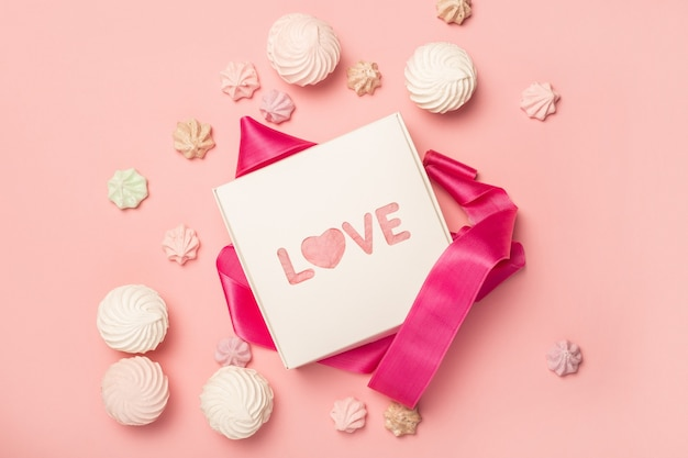 Gift box and gift sweets, marshmallows and meringues on a pastel pink surface