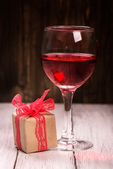 Gift box and glass of pink wine